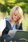 Glückfrau, die an Natur mit Dokumenten arbeitet lizenzfreie stockbilder