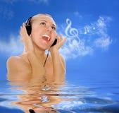Glückfrauen mit in Kopfhörern auf dem blauen Himmel Stockfoto