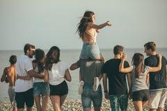 Glücklich bemannt und der Weg der Frau an der Strand Gruppe von den Freunden, die Strandurlaube genießen lizenzfreie stockfotografie