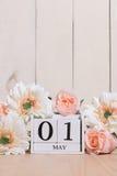 Glücklich der hölzerne Kalender des weißen Blockes des Maifeiertags, der mit Frühlingsblumen auf hölzerner Tabelle verziert wird Lizenzfreies Stockbild