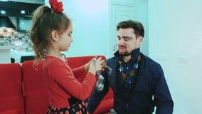 Glücklich, Lächelnfamilie Tochter setzt an ihren Vatischmuck stock footage