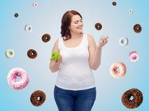 Glücklich plus die Größenfrau, die Apfel oder Plätzchen wählt Stockfotos
