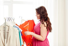 Glücklich plus die Größenfrau, die Kleidung an der Garderobe wählt Stockfotos