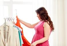 Glücklich plus die Größenfrau, die Kleidung an der Garderobe wählt Stockfotografie