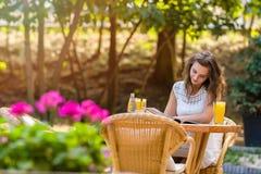 Glücklich, positiv, schön, verlegen das Eleganzmädchen, das am Café sitzt, draußen Lizenzfreies Stockfoto