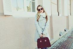 Glücklich und nett, Lächeln blond in der Sonnenbrille junges Modell oder Student im hellen Mantel auf dem natürlichen Straßenhint Lizenzfreie Stockbilder