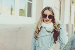 Glücklich und nett, Lächeln blond in der Sonnenbrille junges Modell oder Student im hellen Mantel auf dem natürlichen Straßenhint Lizenzfreie Stockfotos