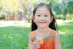 Glücklich vom kleinen Mädchen, das Orangensaft mit befleckt um ihren Mund im Sommergarten trinkt lizenzfreie stockfotos