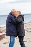 Glückliche ältere ältere Paare, die auf Strand gehen lizenzfreie stockfotos