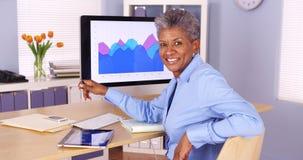 Glückliche ältere afrikanische Geschäftsfrau, die am Schreibtisch sitzt Stockfotografie