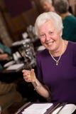 Glückliche ältere Dame in der Gaststätte Stockfoto