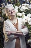 Glückliche ältere Dame im Rosengarten stockfotos
