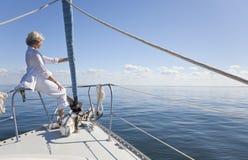 Glückliche ältere Frau auf Bogen eines Segel-Bootes Stockfotografie