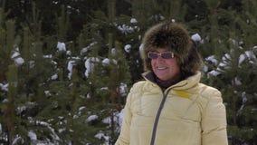 Glückliche ältere Frau des Porträts, die Kamera während des Gehens in Winterwald untersucht stock footage