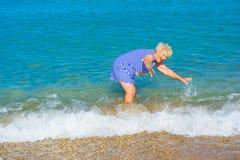 Glückliche ältere Frau, die auf dem Strand genießt stockfotos