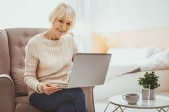Glückliche ältere Frau, die Computer betrachtet lizenzfreies stockfoto