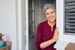 Glückliche ältere Frau, die an der Tür sich lehnt stockbilder