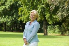 Glückliche ältere Frau, die draußen lächelt Lizenzfreies Stockfoto