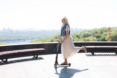Glückliche ältere Frau, die einen Roller reitet stockbild