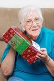 Glückliche ältere Frau, die ihr Weihnachtsgeschenk rüttelt Lizenzfreie Stockfotos