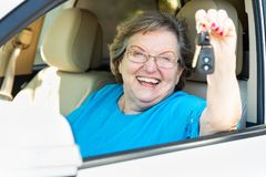 Glückliche ältere Frau, die im Neuwagen hält die Schlüssel sitzt Lizenzfreie Stockfotos