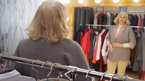 Glückliche ältere Frau, die neue Jacke im Kleidungsspeicher beim Einkauf versucht Reife Frau, die schaut, um bei der Ausstattung  stock video