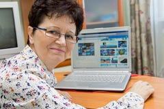 Glückliche ältere Frau, die am Notizbuch sitzt und Bilder auf Reise-Websites schaut Stockfotos