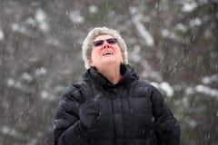 Glückliche ältere Frau, die oben an einem Snowy-Tag schaut Lizenzfreies Stockbild