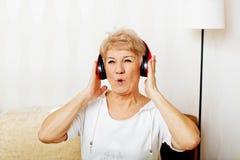 Glückliche ältere Frau, die rote Kopfhörer trägt Stockfotografie