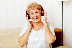 Glückliche ältere Frau, die rote Kopfhörer trägt Stockfotos