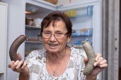 Glückliche ältere Frau, die Schweinefleischleberwürste hält Stockfoto