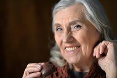 Glückliche ältere Frau, die zu Hause Schokoladenplätzchen isst lizenzfreies stockfoto