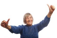 Glückliche ältere Frau, die zwei Daumen als Zeichen der Zustimmung aufgibt Stockbild