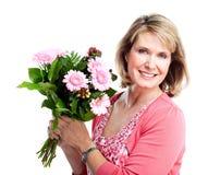 Glückliche ältere Frau mit Blumen. Stockfoto