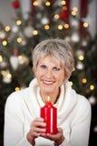 Glückliche ältere Frau mit einer brennenden Kerze lizenzfreie stockfotos