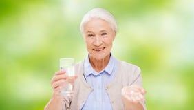 Glückliche ältere Frau mit Wasser und Medizin lizenzfreie stockfotos