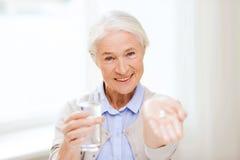 Glückliche ältere Frau mit Wasser und Medizin zu Hause stockbilder