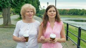 Glückliche ältere Frau und junge Frau geht entlang die Ufergegend und den trinkenden Kaffee Erwachsene Mutter und Tochter, die in stock video