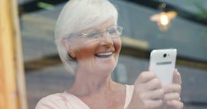 Glückliche ältere Frau, welche die Mitteilung am Handy 4k liest stock video footage