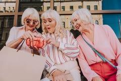 Glückliche ältere Frauen betrachten Neuanschaffungen lizenzfreie stockfotos