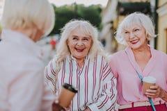 Glückliche ältere Frauen, die ihre Freundin auf der Straße treffen lizenzfreie stockfotos