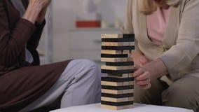 Glückliche ältere Frauen, die mit Freund in Rehabilitationszentrum, Geschicklichkeitsspiel spielen stock footage