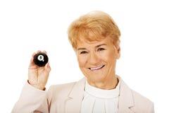 Glückliche ältere Geschäftsfrau, die Billardball acht hält Stockfotografie