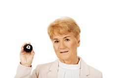 Glückliche ältere Geschäftsfrau, die Billardball acht hält Lizenzfreie Stockfotos