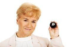 Glückliche ältere Geschäftsfrau, die Billardball acht hält Lizenzfreies Stockfoto