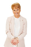 Glückliche ältere Geschäftsfrau, die copyspace oder etwas auf offenen Palmen hält Lizenzfreies Stockbild