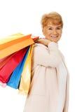 Glückliche ältere Geschäftsfrau, die Einkaufstaschen hält Stockbild