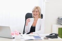 Glückliche ältere Geschäftsfrau, die Kaffeepause hat Stockfotografie