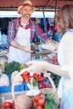 Glückliche ältere Landwirtstellung hinter dem Marktstall, organisches Gemüse verkaufend lizenzfreies stockbild