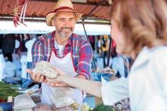 Glückliche ältere Landwirtstellung hinter dem Marktstall, organisches Gemüse verkaufend stockfoto